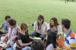 Schüler diskutieren im Park bei einem Picknick